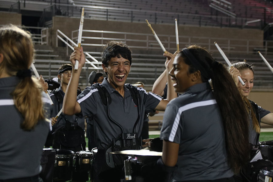 The percussion section celebrates after the half-time show on Sept. 20 at Gupton Stadium.