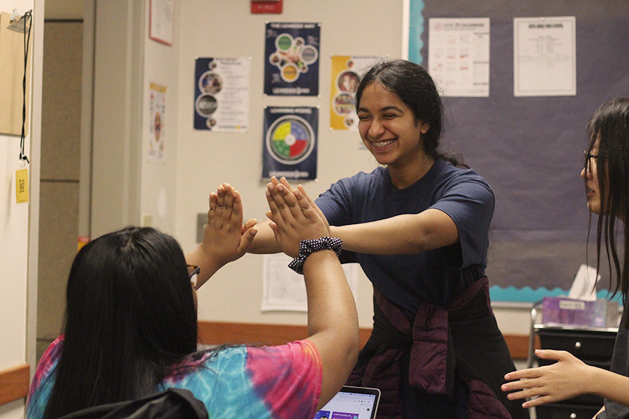 "Excitedly highfiving, sophomore treasurer Ramya Nambala and sophomore Gauri Mishra congratulate each other on successful speeches in their practice during a Youth and Government Meeting.  Nambala and Mishra spent weeks drafting and researching their bills to prepare for the District Conference on Nov. 16. ""We learn self-efficacy, self-advocacy and have confidence in expressing ourselves through speech,"" Nambala said. ""It teaches us democratic leadership and helps us become better citizens."""
